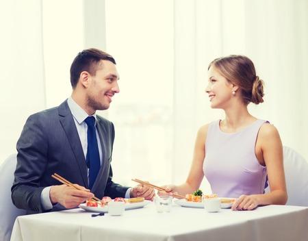 pareja comiendo: restaurante, la pareja y el concepto de vacaciones - sonriente pareja de comer sushi en el restaurante