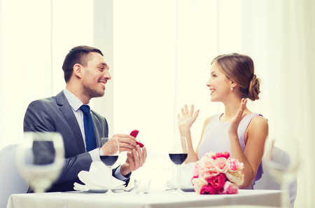 fiance: restaurant, couple and holiday concept - smiling man proposing to his girlfriend at restaurant Stock Photo