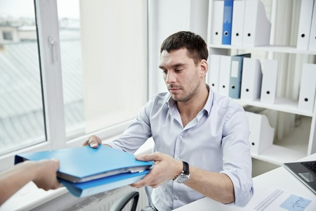 displeased businessman: business, people and paperwork concept - businessman taking folder with papers from secretary in office