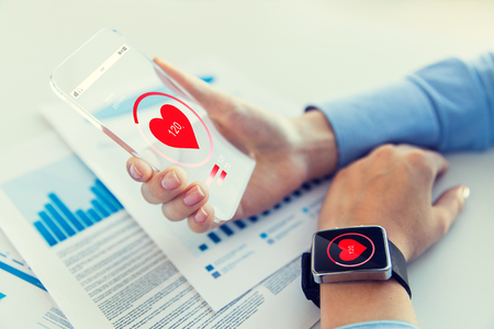 health technology: technology, health care and people concept - close up of woman hand holding transparent smartphone and smartwatch with heart icon at office Stock Photo
