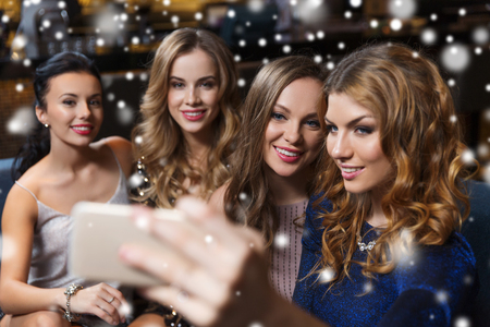 celebration, friends, bachelorette party, technology and holidays concept - happy women with smartphone taking selfie at night club Stock Photo