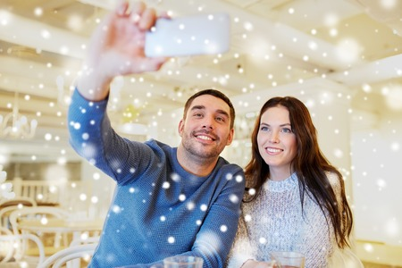 couple dating: people, technology and dating concept - happy couple taking smartphone selfie at cafe or restaurant