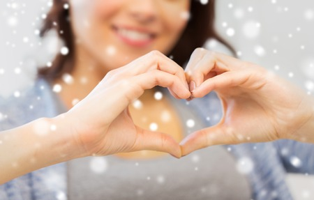 charity  symbol: people, love, valentines day, christmas and  charity concept - close up of happy young woman showing heart with hands over snow Stock Photo