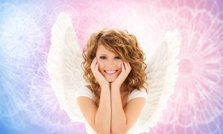 people, holidays and religious concept - happy young woman or teen girl with angel wings over rose quartz and serenity pattern background photo