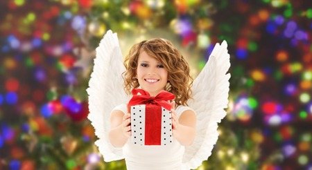 people, holidays, christmas and birthday concept - happy young woman with angel wings holding gift box over lights background photo