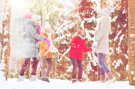 family and friends: love, season, friendship, entertainment and people concept - group of happy men and women having fun and playing snowballs in winter forest
