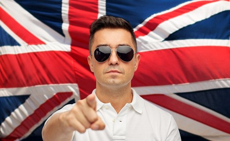 summer, accessories, style and people concept - middle aged latin man in white polo t-shirt and sunglasses pointing finger over brittish flag Stock Photo