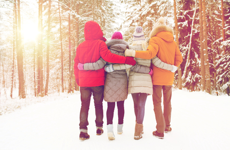 winter holiday: love, relationship, season, friendship and people concept - group of happy men and women walking in winter forest