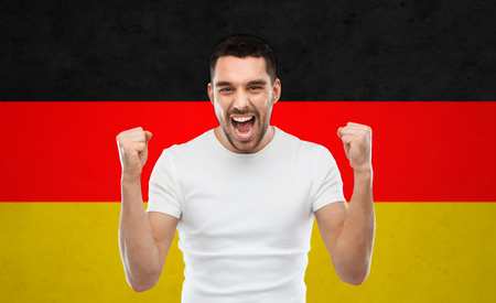middle eastern clothing: emotion, aggression, gesture and people concept - angry young man or immigrant showing fists over german flag background Stock Photo