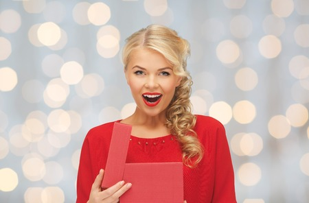 excited woman: christmas, holidays, valentines day, birthday and people concept - happy excited woman in red dress with gift box over lights background Stock Photo