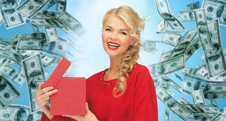 christmas profits: christmas, people, finance and holidays concept - smiling woman in red dress with many gift boxes over blue background and money rain