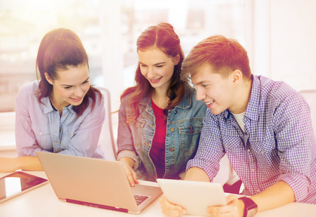 internet school: education, technology, school and internet concept - three smiling students with laptop and tablet pc at school Stock Photo
