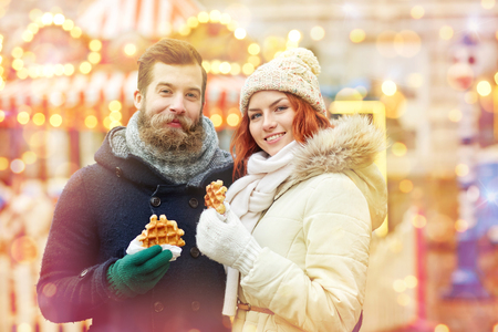woman eat: holidays, winter, christmas and people concept - happy couple in warm clothes walking in old town