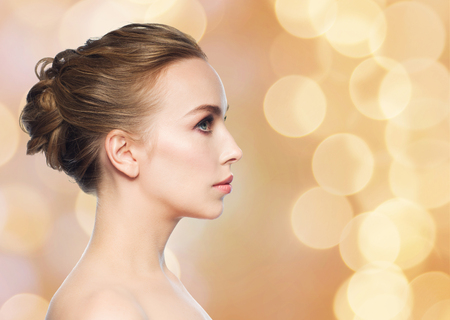 profile face: health, people, plastic surgery and beauty concept - beautiful young woman face profile over holidays lights background