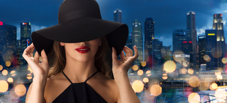 femme fatale: people, luxury and fashion concept - beautiful woman in black hat over nigh lights and singapore city skyscrapers background