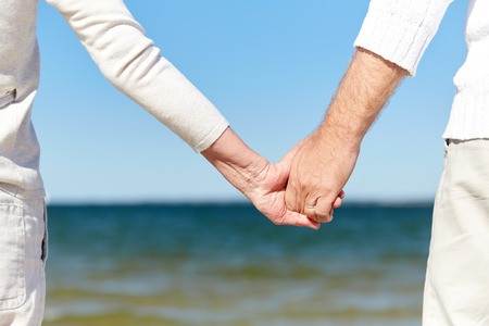 happy senior: family, age, travel, tourism and people concept - close up of senior couple holding hands on summer beach