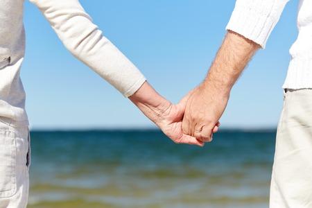 La famille, l'âge, Voyage, tourisme et les gens concept - à proximité de hauts couple se tenant les mains sur la plage d'été Banque d'images - 65121624