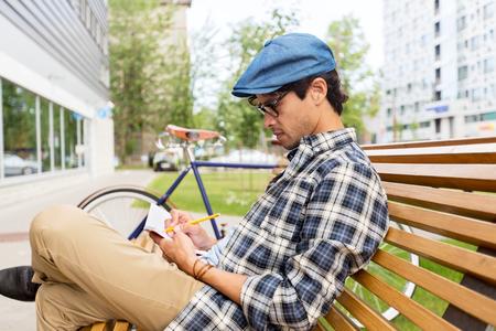 hombre escribiendo: estilo de vida, la creatividad, independiente, la inspiración y el concepto de la gente - hombre creativo con el cuaderno o diario de la escritura se sienta en banco calle de la ciudad