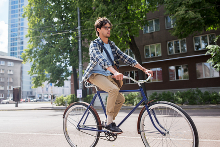 shoulder bag: people, style, leisure and lifestyle - young hipster man with shoulder bag riding fixed gear bike on tallinn city street