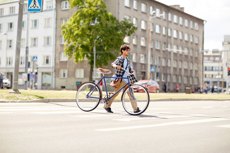shoulder bag: people, style, city life and lifestyle - young hipster man with shoulder bag and fixed gear bike crossing crosswalk on street Stock Photo