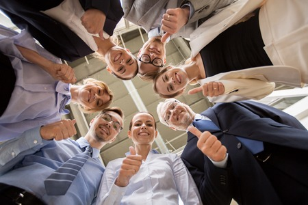 business, people, gesture and teamwork concept - business team snowing thumbs up in circle at office