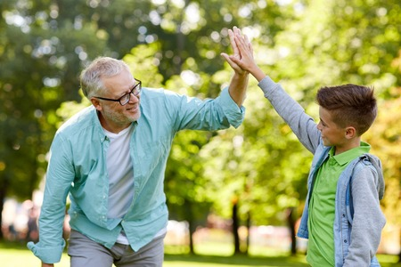 family, generation, gesture and people concept - happy grandfather and grandson making high five at summer park Stockfoto