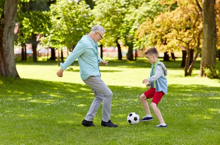 family, generation, game, sport and people concept - happy grandfather and grandson playing football at summer park Stockfoto