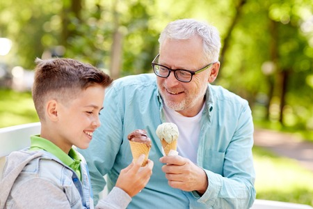 family, generation, communication and people concept - happy grandfather and grandson eating ice cream at summer park Stockfoto