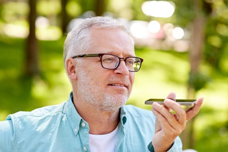 technology, senior people, lifestyle and communication concept - close up of happy old man using voice command recorder or calling on smartphone at summer park