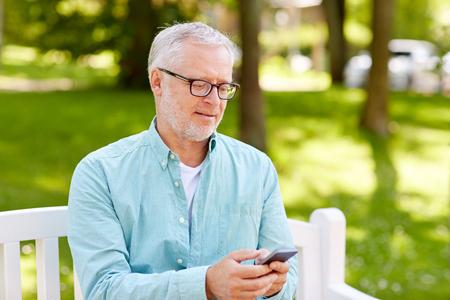 技術、高齢者のライフ スタイルとコミュニケーション コンセプト - 幸せな老人の夏の公園でスマート フォン上にテキスト メッセージと電話番号を