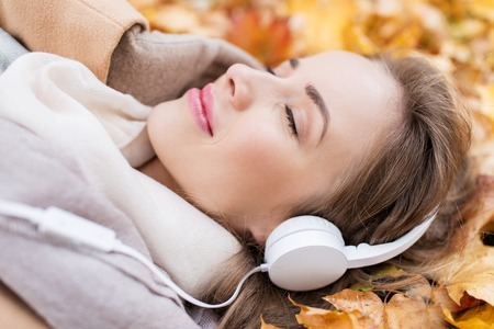 season, technology and people concept - close up of beautiful happy young woman with headphones lying on autumn leaves listening to music