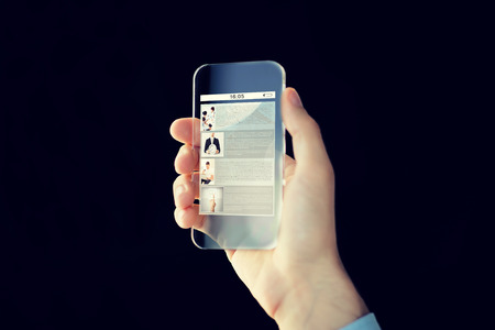 page site: business, future technology, internet and people concept - close up of male hand holding and showing transparent smartphone with web site page on screen over black background