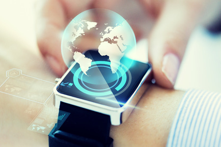 business connection: business, technology, communication, connection and people concept - close up of woman hands globe hologram on smartwatch