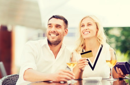 date, people, payment and relations concept  - happy couple with credit card, bill and wine glasses at restaurant terrace Imagens