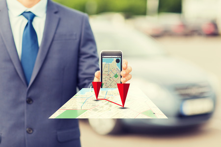 transport, business trip, technology, navigation and people concept - close up of man showing smartphone gps navigator map on screen on car parking Foto de archivo
