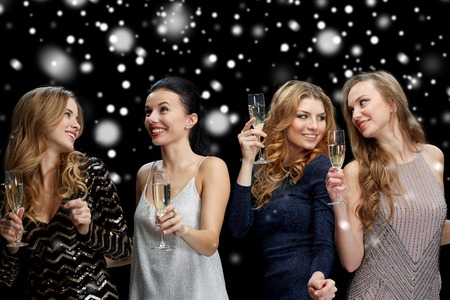 new year party, christmas, winter holidays and people concept - happy women with champagne glasses and dancing over black background with snow Stock Photo