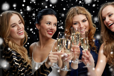 clinking: celebration, friends, bachelorette party and holidays concept - happy women clinking champagne glasses over black background Stock Photo
