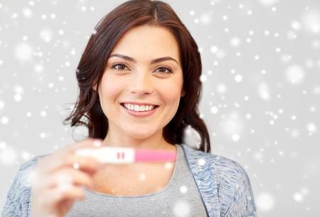 home pregnancy test: pregnancy, fertility, maternity and people concept - happy smiling woman holding and showing positive home pregnancy test over snow