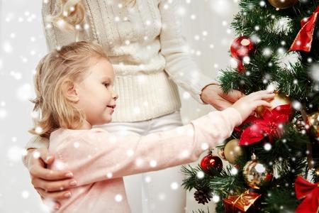 arbol genealógico: familia, Navidad, vacaciones de invierno y concepto de las personas - madre feliz y pequeña hija decorar el árbol de Navidad en casa Foto de archivo