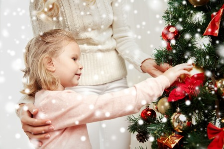 arbol genealógico: family, x-mas, winter holidays and people concept - happy mother and little daughter decorating christmas tree at home