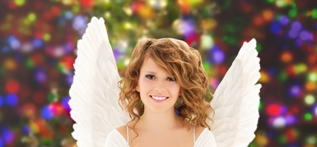people, holidays, christmas and party concept - happy young woman or teen girl with angel wings over lights background photo