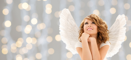 people, holidays, christmas and religious concept - happy young woman or teen girl with angel wings over lights background photo