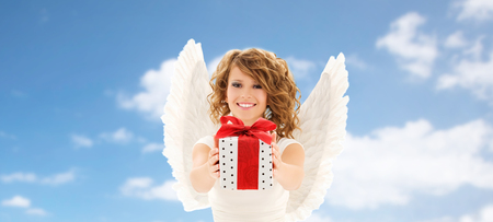 people, holidays, christmas, birthday and religious concept - happy young woman with angel wings holding gift box over blue sky and clouds background photo
