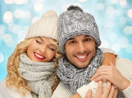 people, christmas, holidays and new year concept - happy family couple in winter clothes hugging over blue lights background 写真素材