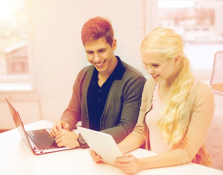 school, education, technology and internet concept - two teens with laptop and tablet pc at school photo