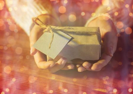 personas saludandose: navidad, días de fiesta, presenta, año nuevo y el concepto de personas - cerca de la mujer manos caja de regalo o paquete envuelto en papel marrón electrónico con tarjetas de felicitación más luces que sostiene