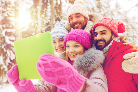 winter holiday: technology, season, friendship and people concept - group of smiling men and women taking selfie tablet pc computer in winter forest Stock Photo