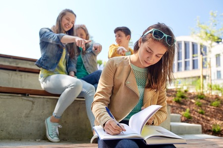 social outcast: education, bullying, high school, social relations and people concept - unhappy student girl with book suffering of classmates mockery