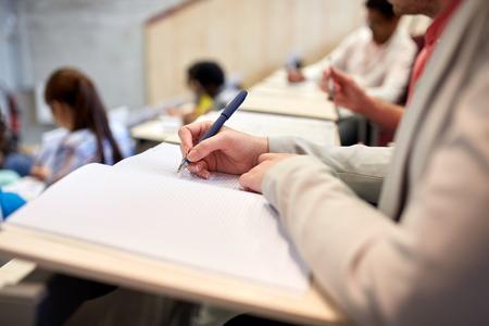 la educación, la escuela secundaria, la universidad, el aprendizaje y el concepto de la gente - estudiante escribir en el cuaderno en el examen o una conferencia