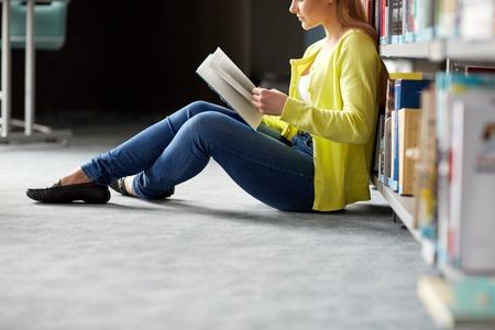 mujeres sentadas: la educación, la escuela secundaria, la universidad, el aprendizaje y el concepto de la gente - chica estudiante libro sentado en el piso en la biblioteca leyendo sonriendo
